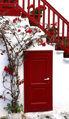 Mykonos, Greece. Check out the balance of red color in this room. With a door, staircase and plants set up, this is an interior designer's dream come true. Architects and designers are always looking for the next best thin.  Terrazzo is a material is just as colorful and has many design possibilities.  Doyledickersonterrazzo.com