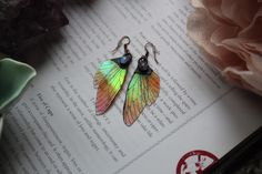 Whimsical fairy wing earrings in orange with a beautiful golden glow. They feature a rainbow moonstone cabochon, which is set in antiqued copper.