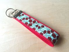 """Fabric wristlet keychain, key fob - Red Peony. Still digging around your purse for your keys? Make them easy to find with this fabric wristlet keychain. At 5"""" it's long enough to fit around most wrists comfortably. You can also use it to attach your favorite clutch to carry around town, or attach it to a zipper on your luggage or overnight bag for a colorful luggage spotter. As handmade items go, pattern placement may vary. Your keychain might be slightly different from the picture shown...."""