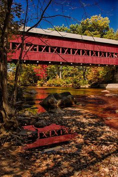 Swiftriver covered bridge. Conway New Hampshire with real reflection in a pool in the river bed.