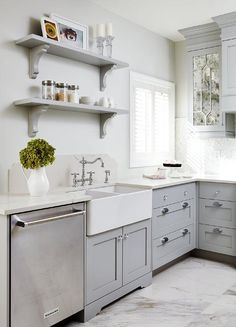 Beautiful gray kitchen features a dual farmhouse sink fixed above gray shaker cabinets adorning glass knobs and beneath gray shelves accented with gray corbels and mounted beside a window to a gray wall.