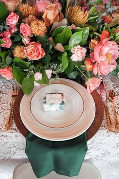 Simple place settings with emerald-colored napkins and bright flower arrangement {Tana Photography}