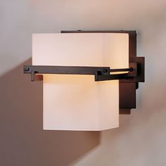 Direct wire wall sconce featuring a tall stepped box diffuser within a forged iron wraparound support.