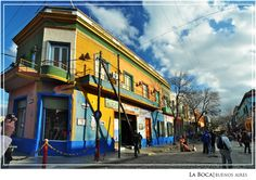 La Boca, Buenos Aires. A typical scene from La boca, where you could see street artists having their own gimmicks on entertaining lots of tourist and the attractive colorful houses. Pardon the hand and camera on the left side, tourists simply don't mind others spaces.