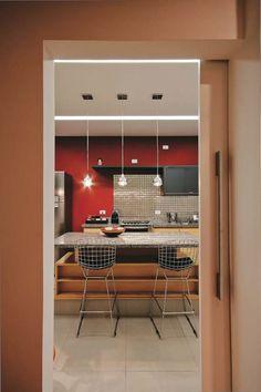Com uma mesa de jantar espaçosa, a cozinha deste apartamento em São Paulo aproxima os moradores dos convidados enquanto se prepara a comida. A iluminação, idealizada pela arquiteta Roberta Banqueri, atende a todas as funções. No rasgo do forro de gesso (20 cm de largura), as fluorescentes T5 oferecem ótimos fluxo luminoso e índice de reprodução de cores. Para clarear a mesa por inteiro, alocaram-se três pendentes (Tec Lutres) a 60 cm de distância entre si. Eles usam lâmpadas halopin de 50 w…