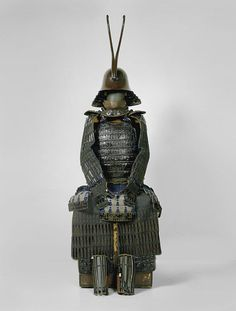 """Hosokawa Clan Armor. Etchu zunari kabuto, hon iyozane dou gusoku, 1800s, the later Edo period armors in the Hosokawa collection reflect the troubled times at the end of the feudal era, and the shogunates end. Dark blue was preferred; excessive ornament was avoided. This suit of """"Sansai-style"""" armor, worn by the 14th-gen family head, Hosokawa Morihisa (1839–1893), in the style of his ancestor Hosokawa Sansai more than two hundred years earlier."""