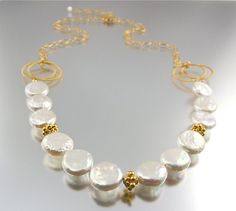 This gold coin pearl necklace is strikingly beautiful with a timeless appeal. Featuring a strand of iridescent natural white freshwater coin pearls with an organic feel and embellished with gold vermeil fancy bicone daisy beads at intervals, this necklace is stunning. Pearls are suspended from a pair of gold vermeil twisted rings on each side for a stylish accent and 14k gold filled long and short chain. Necklace is adjustable up to 22 inches long for a perfect fit, and fastens with a gold…