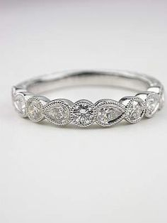 Antique Style Wedding Band with Pear Brilliant Cut Diamonds  Pear cut diamonds alternate with round diamonds to create a shimmering half circle around her finger. Delicate teardrops and circles come together in this pretty antique style wedding band. Each of the nine geometric elements is accented with a diamond. They total 0.54 carats. This is a new wedding band in the antique style. Size 6.