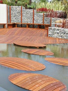 Pond with wood walkway to access deck; Gabions (steel framed boxes filled with stones) create the wall and seating