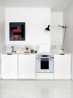Cozinha branca com quadro colorido