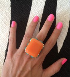 matte pink nails and an orange/turquoise ring.