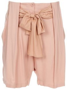 Nude loose fit shorts from By Malene Birger featuring a front fastening with tonal button, a waistband with tie up bow, loose panels to the front, with side pockets.