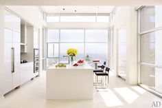 Painted in a Benjamin Moore white, the kitchen is centered by an island clad in Caesarstone | archdigest.com