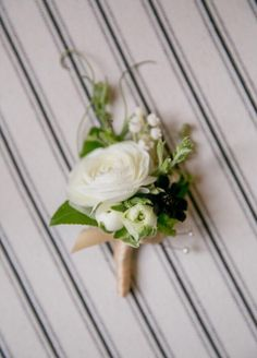 Lily of the valley, chocolate cosmos and a white ranunculus boutonnière