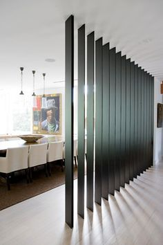 A black painted steel privacy screen allows a peek into the living and dining area and garden. The blades have sleek, modern visual appeal and direct light into the open plan. They also separate sections of the house without enclosing them in solid walls