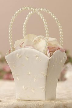"Ivory Pearl Handle Satin Flower Girl Basket  A strand of pearls make up the handles of this 8.5"" tall flower girl basket. The simple satin of this basket makes it a perfect match for almost any wedding decor."