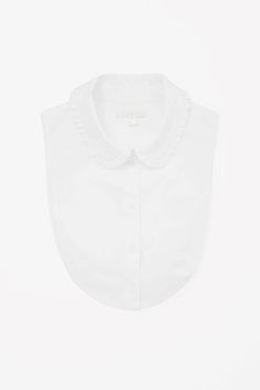 Made from crisp cotton, this mock shirt is a curved bib shape with a frill detailed collar. Designed to be layered under tops, giving the illusion of a shirt, it has subtle elastic straps to keep it in place.