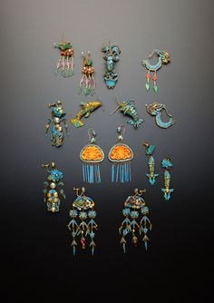 SEVEN PAIRS OF CHINESE GILT METAL AND KINGFISHER FEATHER EARRINGS QING DYNASTY Variously formed as fish, dragons, foliate arrangements and insects, decorated with pearls, coral, jadeite and other stones, one pair mounted with amber butterfly plaques, together with a single model of a grasshopper perched on a jardinière of flowers, 9cm max. (15) Provenance: a private collection, London. Cf. The National Palace Museum, Royal Style, Qing Dynasty and Western Court Jewelry, pp.136-137 for related…