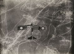 A french biplane flying over the battlefields of Verdun, 1916.