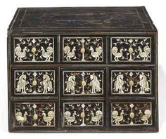AN ANGLO-INDIAN IVORY AND EBONY TABLE CABINET LATE 17TH CENTURY  The rectangular top inlaid with shaped reserves, above six variously-sized drawers decorated with exotic birds and foliate sprays, the sides with floral reserves and engraved drop handles, some restorations 11½ in. (29 cm.) high; 17 in. (43.5 cm.) wide; 12¼ in. (31.5 cm.) deep. Price Realized   $25,935 Estimate $6,408 - $9,612