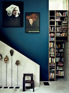 mur bleu canard et portraits extravagants, bibliothèque originale