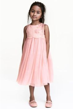Sleeveless tulle dress with sequined embroidery at the top, a wide, pleated skirt and concealed zip at the back. Lined.