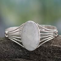 Rainbow moonstone is mesmerizing in this beautiful design by Shanker. The bracelet juxtaposes the gem with shining sterling silver, making the cuff a glamorous fashion accessory. Twin garnets adorn each side.