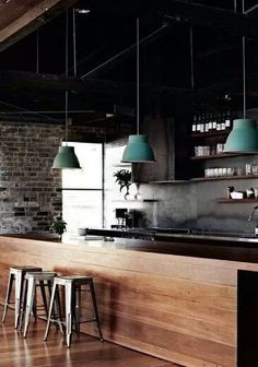I love the contrast of the black wall with the timber-clad bench and the turquoise lamps.
