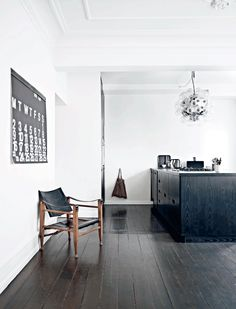 black floorboards, black kitchen cupboards, white walls and black and wooden chair