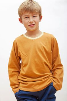 Organic cotton jersey long sleeve t-shirt in orange with yellow V-neck collar. Sizes 9 mos to youth 10.