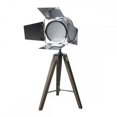 Gorgeous!! A silver coloured metal tripod lamp complete with shutters and standing on a wooden and metal tripod. The lamp measures 17 x 16 x 16 cm and fixes into the tripod legs measuring 42 cm long. The overall height of the lamp is approx 70 cm.