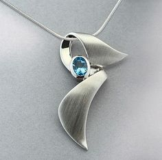 This brilliant blue topaz is bezel set and sits on a contemporary silver ribbon blowing in the caribbean wind. This is a unique, nicely made pendant that gives the awareness symbol a fresh twist. This