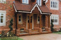 Oak beams with curved braces and brick piers make an attractive canopy on the front of this house. Brick Porch, Porch Roof, Screened In Porch, Porch Swing, House Canopy, Porch Canopy, Door Canopy, House With Porch, House Front
