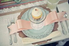 Decor ~ Think blush pink, baby blues and pale yellow. I adore the styling of the tea party bridal shower below with mismatched table cloths and chairs ~ the satin ribbon and cupcake place settings are just so inviting!