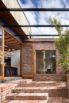 Wood framed glass doors open the dining area of this extention to the backyard, where there's a brick patio, pool and yard. Click through to see more photos. #BrickPatio #Patio #Architecture #OutdoorSpace