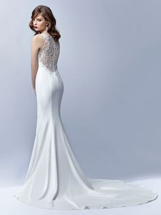 Va-va-voom. Understated elegance and simple glamour are embodied in this full-length, figure-hugging stretch georgette mermaid gown showcasing a deep V-neckline and jaw-dropping low illusion back embellished with intricate embroidery, beading and pearl accents, pearl buttons, and an invisible zipper.