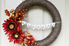 Vibrant colors + a bit of bunting = one sophisticated wreath.  Get the tutorial at Love of Family and Home.   - CountryLiving.com