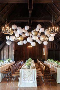 Alegría y formalidad. Globos blancos en el techo del salón de recepción decorado con inspiración botánica, en blanco y dorado.
