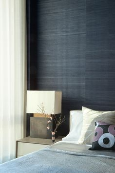 Deep indigo sea grass paper provides a rich but earthy backdrop for this guest bedroom.