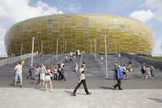 From afar, the Gdansk football stadium looks like a huge drop of precious amber .