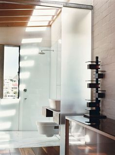 After a gut renovation, a onetime gunpowder store became architect Brian Zulaikha's residence in Balmain Point, Australia. In the upstairs bathroom, the sun cuts down through skylights, casting rhythmic shadows of roof beams onto the floor and walls. The bathroom includes a cantilevered toilet by Catalano. Read the whole story here.  Photo by: Roger D'Souza