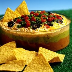 Colorful layers of refried beans, guacamole, sour cream, cheese, spicy tomatoes, olives and onion for a casual party dip
