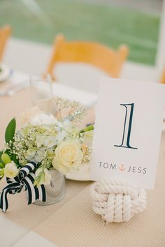Simple Burlap runner with small arragements and nautical knot for table numbers - perfect for a seaside wedding