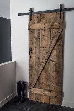 Hall d'entrée avec garde-robe de type walk-in et porte coulissante composée de planches de bois récupérées. Crédit photo: Photographie Atypic.