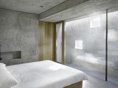 Edles Schlafzimmer mit Betonwand und Lichthof zur Isolierung