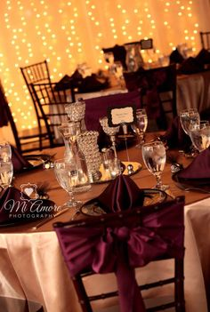 Burgundy sashes with bling centerpieces on gold linen.