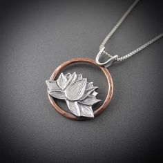 "A delicate yet strong flower, the Lotus blossom has been adopted as the symbol of the Michigan Lupus Foundation and we are proud to donate a portion of the proceeds of this pendant to research, education and outreach for those living with Lupus in Michigan. Product features: Eco-friendly recycled sterling silver and copper. Size = 7/8"" (2.2cm) in diameter. Handcrafted in Marquette, Michigan. Customize this pendant: Add an engraving - personalize your pendant with a special mess..."