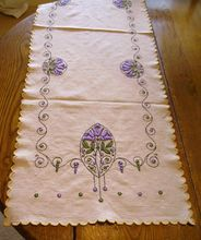 All Hand Embroidered Arts & Crafts Linen Table Runner. long linen table runner. It measures approx. 52.5 inches long. The linen is a light ecru color. The edges are scalloped and embroidered with a light yellow thread. The embroidered in the center is all hand done. It has a floral, dot, and scroll motif. The scrolls are done in black thread. The flowers (tulips)and dots are done in a lilac purple and green. The tulips are slightly padded to give a 3D look. $175. Close-up photos at link.