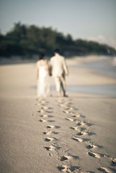 I love the perspective of this wedding photograph, focusing on the footprints of the bride and groom on the beach. Very cool.