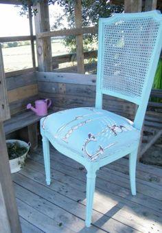 Antigua silla de rejilla lacada en decape azul. Tapizada en loneta estampada con motivos de candelabros y lámparas.